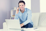 Laughing casual man using laptop and phoning