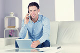 Smiling casual man using tablet and phoning