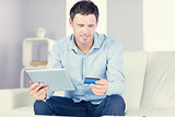 Smiling casual man using tablet and credit card