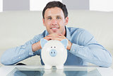 Cheerful casual man resting head on piggy bank