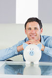 Happy casual man resting head on piggy bank
