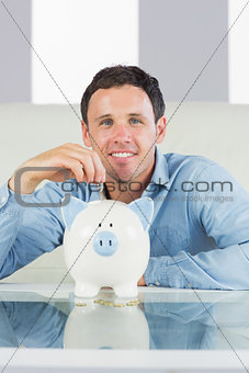 Smiling casual man putting coin in piggy bank
