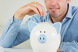Happy casual man putting coin in piggy bank