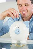 Laughing casual man putting coin in piggy bank