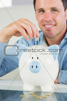 Attractive casual man putting coin in piggy bank