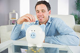 Good looking casual man putting coin in piggy bank and looking down