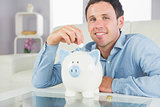 Handsome casual man putting coin in piggy bank smiling at camera