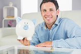 Handsome casual man holding piggy bank
