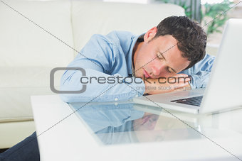 Tired casual man sleeping with head resting on table
