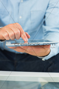 Close up of man holding and using tablet
