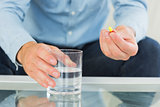 Close up of man holding glass of water and pill