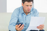 Serious casual man holding calculator paying bills looking at document