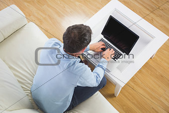 High angle view of casual man typing on laptop