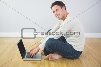 Casual content man sitting on floor using laptop