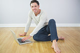 Casual cheerful man sitting on floor using laptop