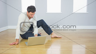 Casual handsome man sitting on floor using laptop