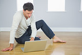 Casual good looking man sitting on floor using laptop