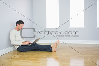 Casual good looking man leaning against wall using laptop
