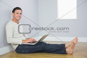 Casual smiling man leaning against wall using laptop