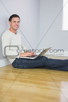 Casual cheerful man leaning against wall using laptop