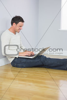 Casual laughing man leaning against wall using laptop