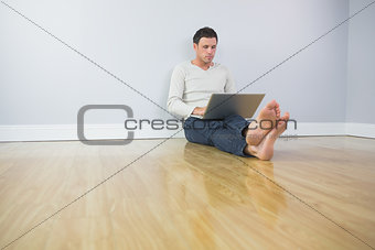 Casual handsome man leaning against wall using laptop