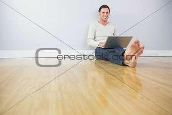 Casual happy man leaning against wall using laptop