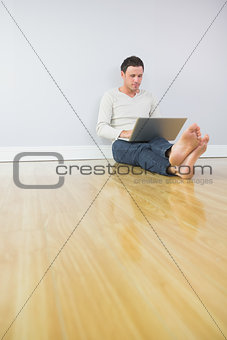 Casual attractive man leaning against wall using laptop