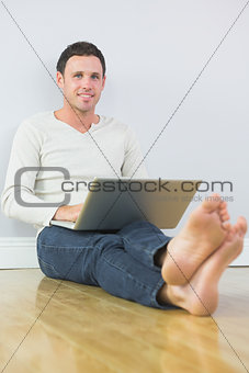 Casual lucky man leaning against wall using laptop