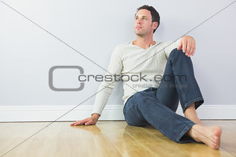 Casual pensive man leaning against wall looking up