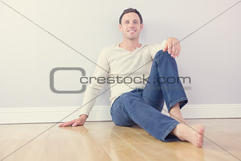 Casual cheerful man leaning against wall looking at camera