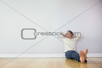Casual pensive man leaning against wall with crossed arms