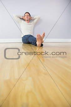 Casual smiling man leaning against wall with crossed arms