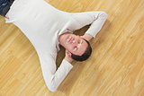 Casual calm man lying on floor with closed eyes