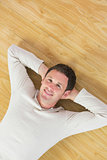 Casual smiling man lying on floor looking at camera