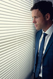 Stern handsome businessman looking out of window