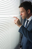 Stern handsome businessman looking through roller blind