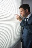 Unsmiling handsome businessman looking through roller blind