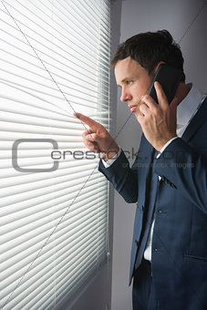 Stern handsome businessman looking through roller blind phoning
