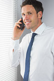 Smiling handsome businessman phoning