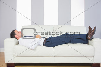 Calm handsome businessman lying on couch