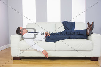 Tired handsome businessman lying on couch