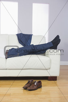 Close up of male legs in suit lying on couch