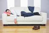 Calm handsome businessman sleeping on couch