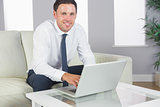Cheerful handsome businessman working at laptop