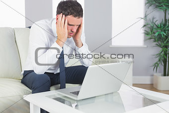 Upset handsome businessman working at laptop