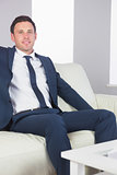 Smiling handsome businessman relaxing on couch