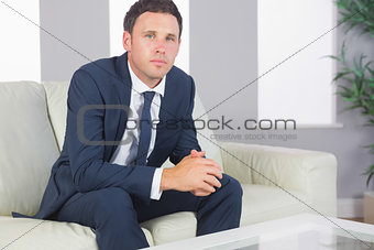 Calm handsome businessman relaxing on couch