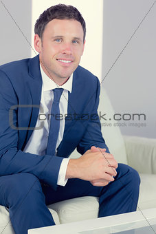 Cheerful handsome businessman relaxing on couch