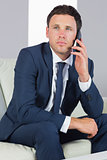 Unsmiling handsome businessman phoning and sitting on couch
